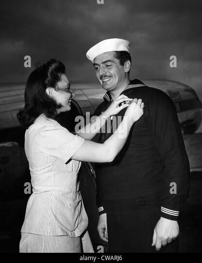 American actor and Coast Guardsman Victor Mature (right), receiving campaign ribbons from Juanita Ferrara (left), - Stock-Bilder