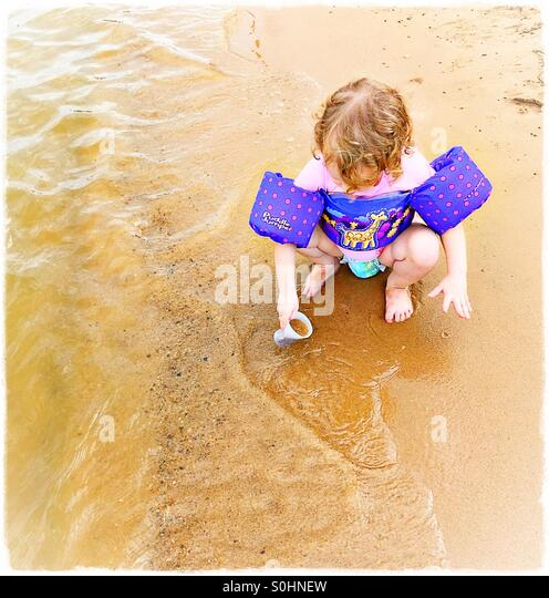 Toddler playing at the beach - Stock Image