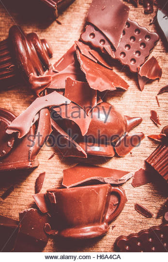 Chocolate in destruction with a crash of smashed chocolate in a morning tea demolition with moulded chocolate dessert - Stock Image