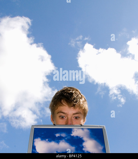 surprised person looking over laptop screen with cloud images representing cloud computing - Stock Image