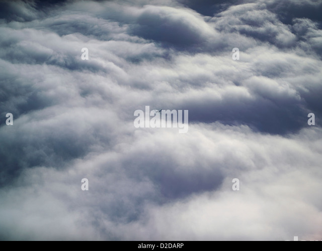Pilots eye view above the clouds, with a light aircraft flying on an opposite course below, shot over Shropshire, - Stock Image