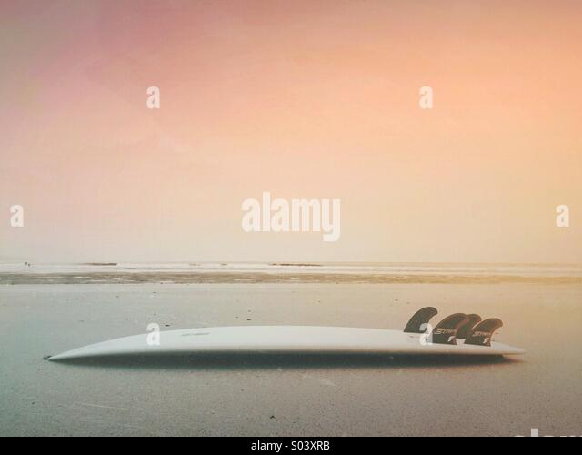 Surfboard on a beach with waves and the sea in the background at sunset - Stock Image