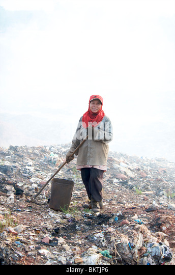 The poor hand sorting waste for recycling at a landfill site in Thailand. - Stock Image