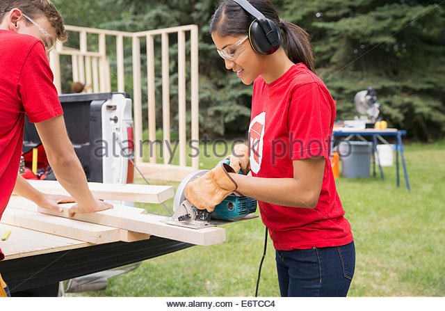Volunteers using table saw at tailgate - Stock Image