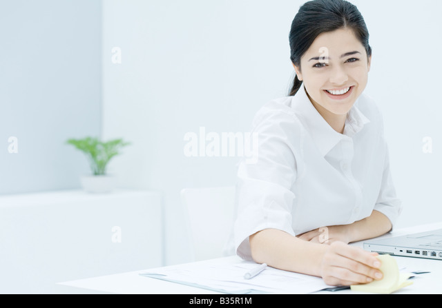Young woman fidgeting with adhesive notes, smiling at camera - Stock-Bilder