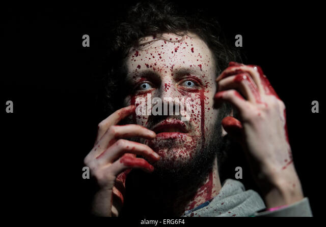 A male zombie with face splattered with blood and hands raised. - Stock Image