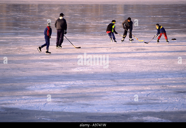 Playing ice hockey on a frozen Canadian lake. - Stock Image