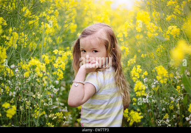 Girl looking over her shoulder in a meadow of yellow flowers - Stock Image
