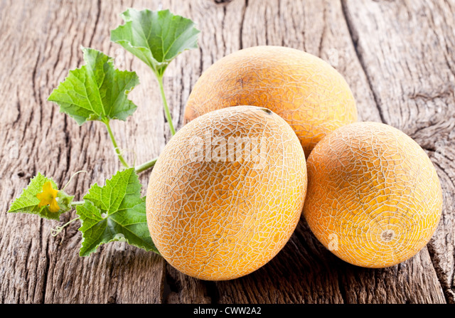 Three melon with the leaves on the old wooden table. - Stock Image