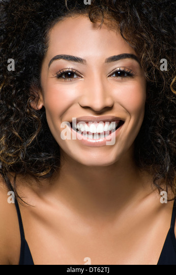 Close up studio portrait of happy young woman - Stock Image