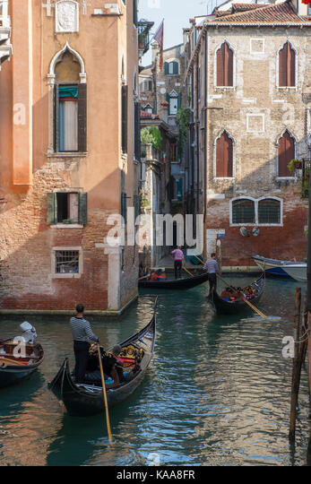 Venice canals and Gondoliers steering their Gondolas - Stock Image