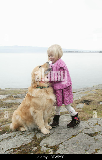 young girl with her golden retriever  outdoors near lake - Stock Image