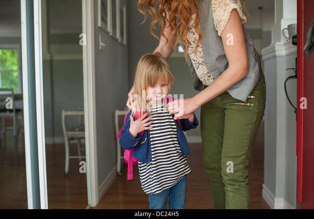 Mother helping daughter to put on rucksack - Stock Image
