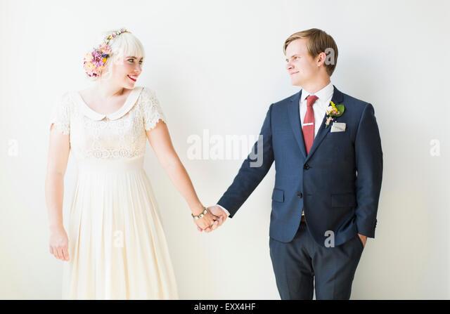 Smiling newlywed couple in studio - Stock Image