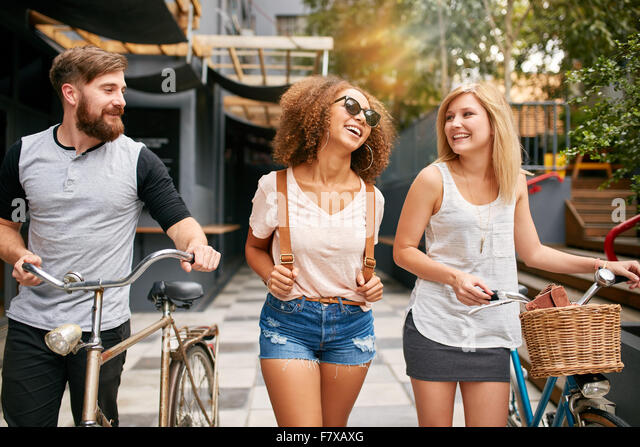 Happy young people walking down the city street with their bicycles and smiling. Young man and women on road with - Stock Image