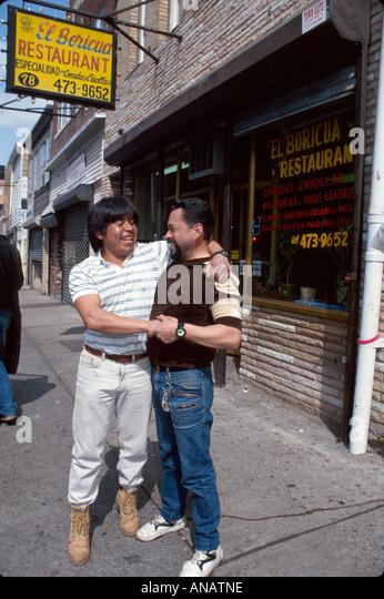 New Jersey Passaic Hispanic men hug greet sidewalk affection - Stock Image