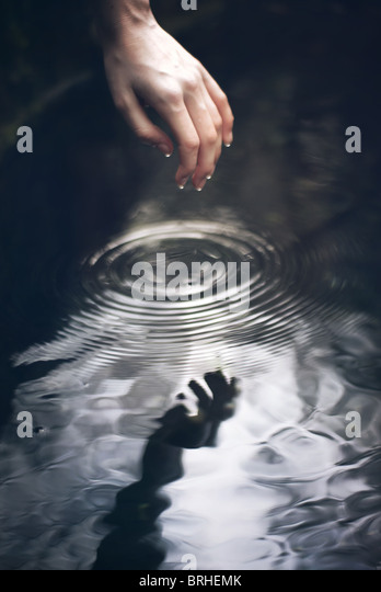 hand going into water - Stock Image