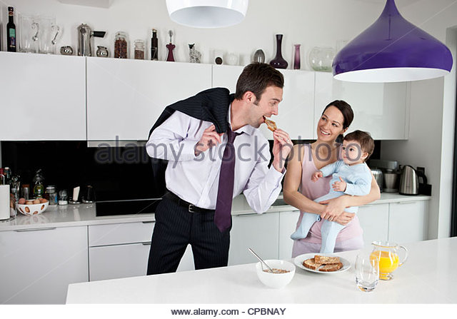 A couple and their baby son in the kitchen, father going off to work - Stock-Bilder