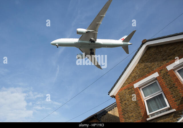 London, UK. An aircraft flies over a house in Hatton Cross on the approach to land at Heathrow Airport. - Stock Image