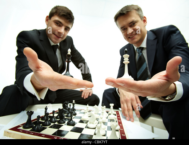 Image of successful businessmen looking at camera while showing bishop figures - Stock Image