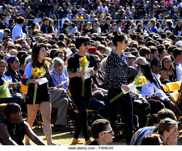 Students carry flowers as they attend a memorial event for the six UCSB students killed and 13 wounded in a shooting - Stock Image