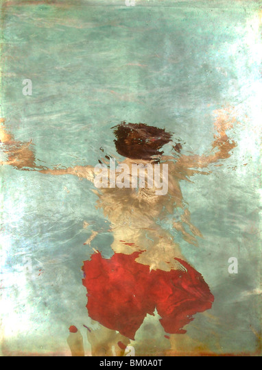 A teenager floating face down in a swimming pool wearing red shorts - Stock-Bilder