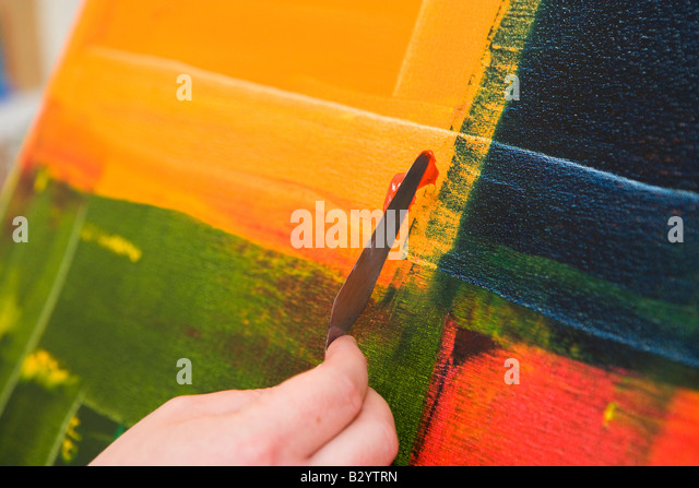 an abstract painting being created by an artist using a knife to apply paint - Stock Image