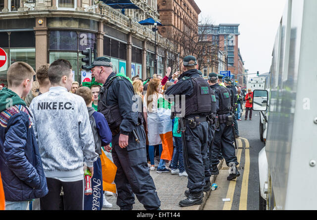 Rival groups of republicans draped in Irish Tricolors and Unionists waving Union Flags face each other in front - Stock Image