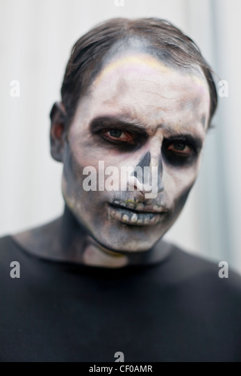man made up with face paint to look like a skeleton - Stock Image