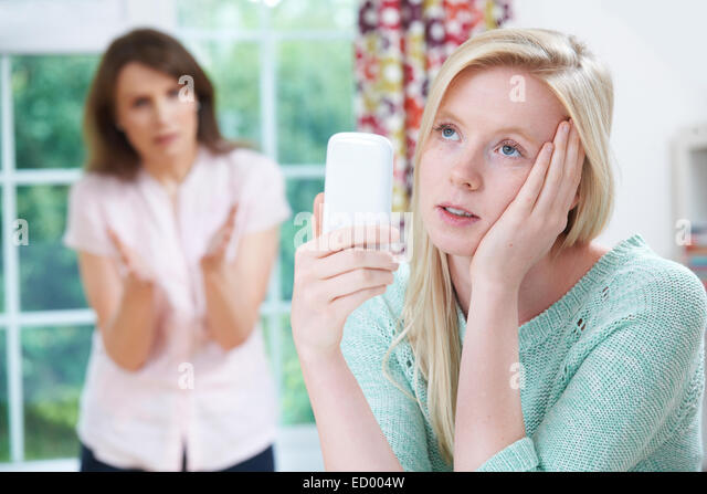 Mother Arguing With Teenage Daughter Over Use Of Mobile Phone - Stock Image