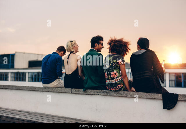 Rear view shot of young men and women sitting together on rooftop. Mixed race friends relaxing on terrace during - Stock Image