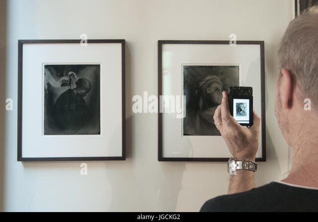 Venice, Italy. 05th July, 2017. A visitor takes a picture of the  photographs on display by artist Khadija Saye - Stock Image