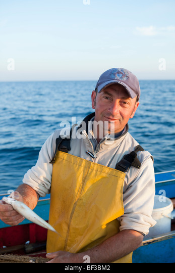 fisherman on his boat, laughing - Stock Image
