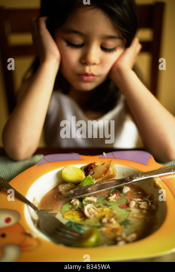 Five year old girl becomes choosey about her food and decides she no longer likes eating Brussel sprouts - Stock Image