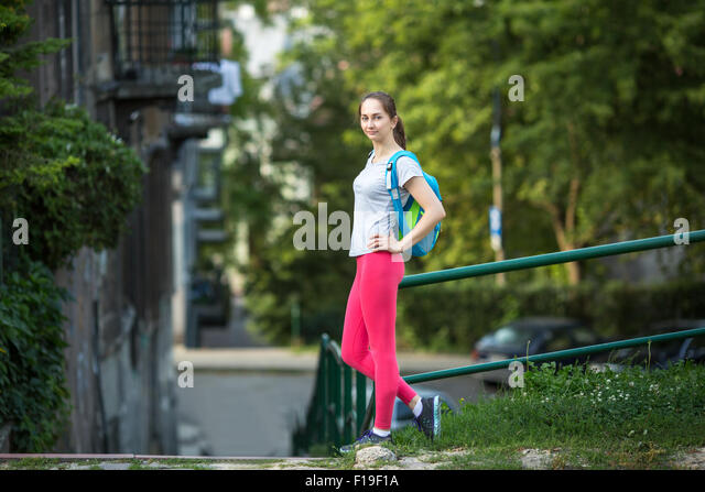 Young sporty woman standing outdoors after a workout in summer day. Workout outdoors. - Stock Image