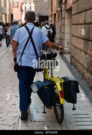 A Postman pushing his bike in a street in Verona Italy - Stock Image