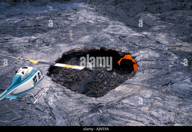 Big Island of Hawaii Volcano National Park Helicopter hovering over lava flow - Stock Image