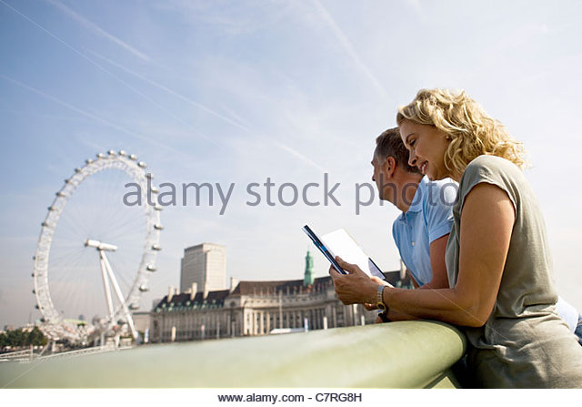 A middle-aged couple standing near the London Eye, looking at a guidebook - Stock Image
