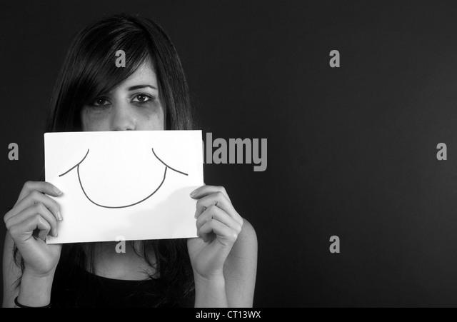 Crying teenage girl holding fake smile - Stock Image