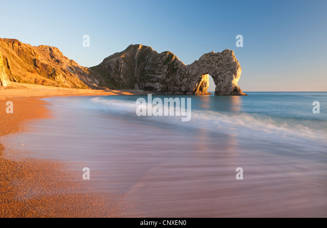 Waves sweeping onto the deserted beach at Durdle Door, Dorset, England. Winter (January) 2011. - Stock Image