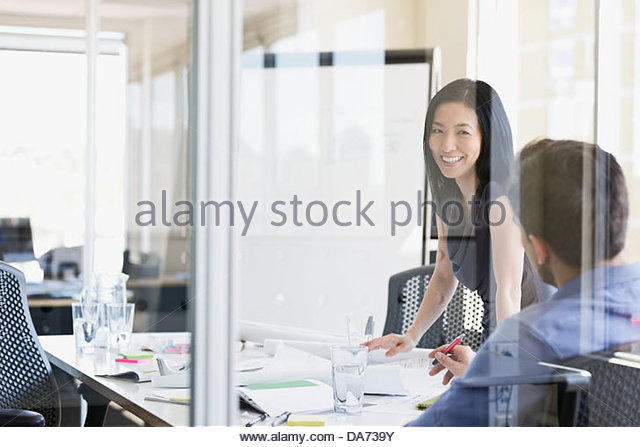 Business people reviewing paperwork at desk in office - Stock-Bilder