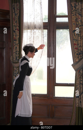 A chamber maid gazes out of a window in a stately home. - Stock-Bilder