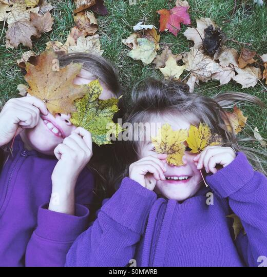 Sisters playing with the leaves of autumn - Stock Image