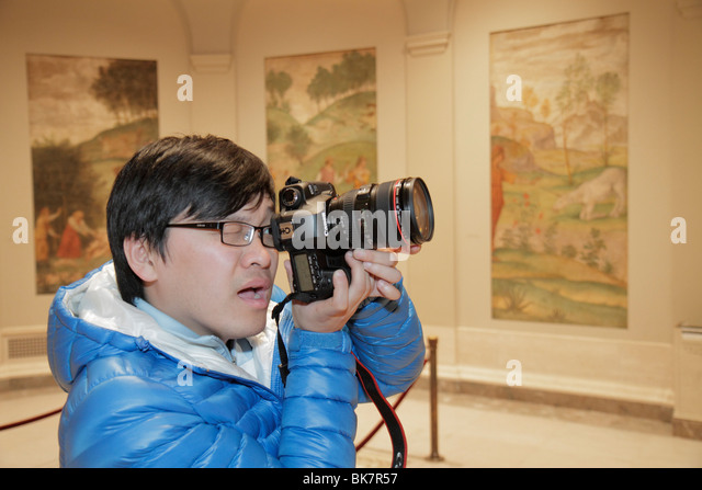 Washington DC National Gallery of Art West Building museum exhibition panels Asian man photographer Canon camera - Stock Image