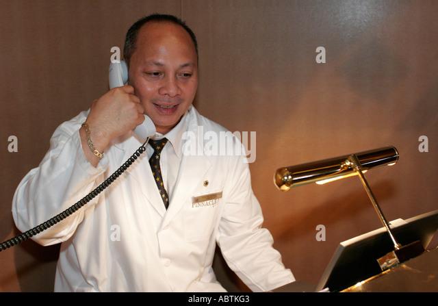 Puerto Rico Atlantic Ocean Holland America Line ms Noordam Pinnacle Grill Asian male manager telephone - Stock Image