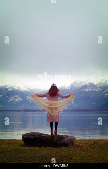 a woman in a pink coat with a white shawl is standing at a lake - Stock Image