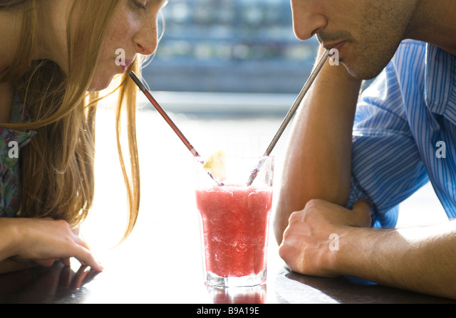 Couple sharing cool drink, cropped - Stock Image