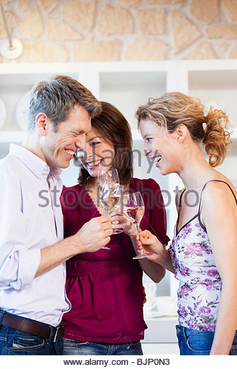 People clinking glasses of white wine - Stock Image