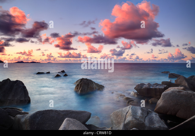 Clouds over the Baie Ste Anne at sunset as seen from the north end of La Digue in the Seychelles - Stock Image