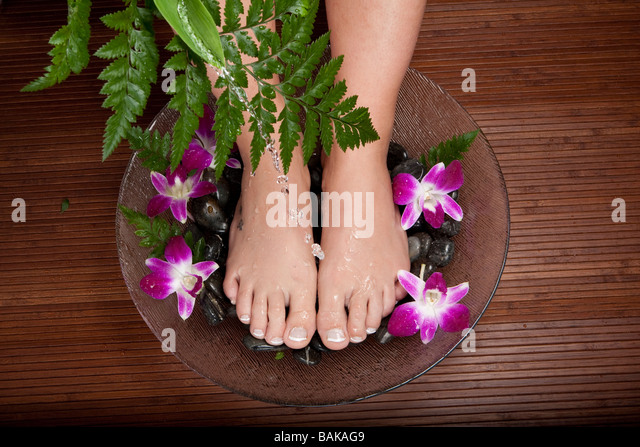 Female feet being washed in a bowl with pebble and flowers - Stock Image